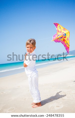 Summer vacation - Cute boy flying kite beach outdoor