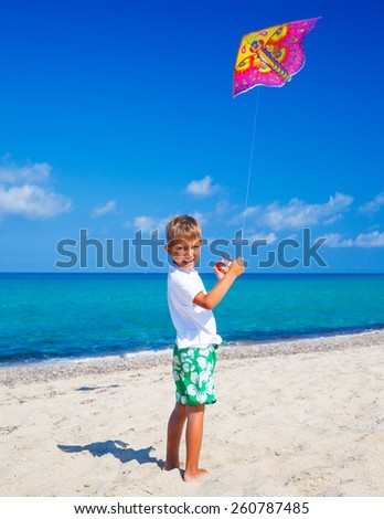 Summer vacation - Cute boy flying kite beach outdoor.