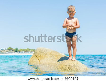 Summer vacation - Cute boy standing on the stone in the transparent sea - stock photo