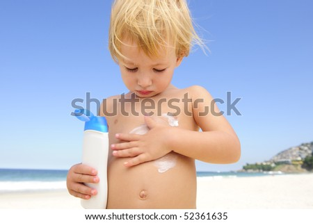 summer vacation: cute child applying  sunscreen  at the beach