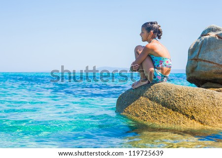 Summer vacation - Cute girl sitting on the stone in the transparent sea - stock photo