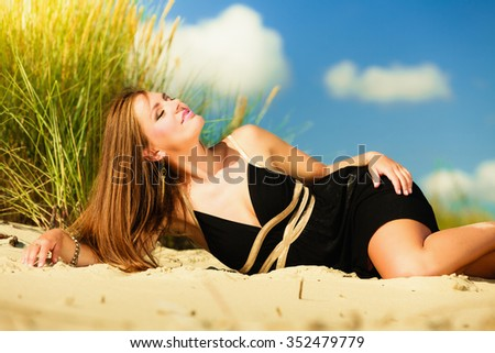 Summer vacation day free time concept. Sitting woman body sunbathing delight on beach seaside.