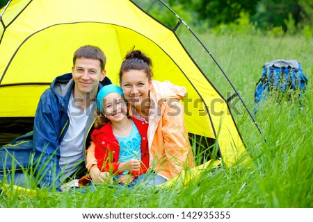 Summer vacation. Family of three in tent in camping on the nature. - stock photo