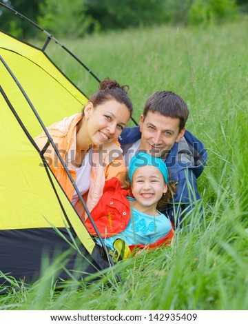 Summer vacation. Family of three in tent in camping on the nature. Vertical view - stock photo