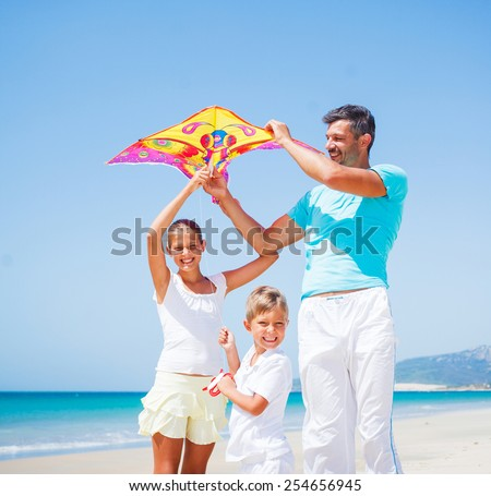 Summer vacation - Father with is two kids flying kite beach outdoor. - stock photo