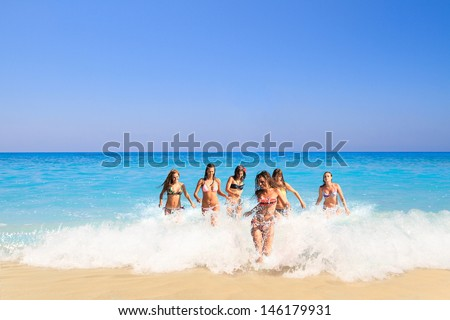 Summer vacation group of six girls running in the sea  - stock photo