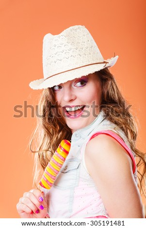 Summer vacation happiness concept. Smiling cheerful woman in straw hat eating popsicle ice cream orange background - stock photo
