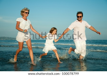 Summer vacation - happy family playing at the beach - stock photo
