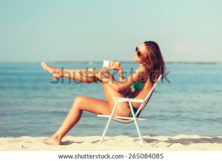 summer vacation, holidays and people concept - smiling young woman sunbathing in lounge on beach - stock photo