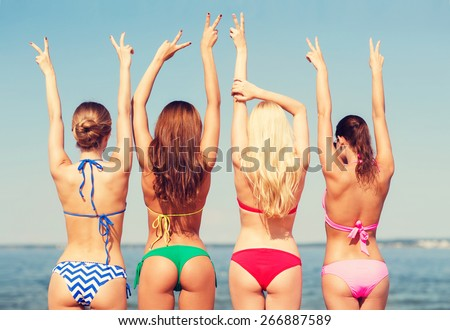 summer vacation, holidays, gesture, travel and people concept - group of young women showing peace or victory sign on beach fom back - stock photo