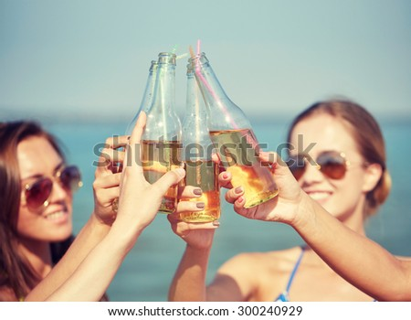 summer vacation, holidays, party, travel and people concept - close up of happy young women with drinks clinking bottles on beach - stock photo