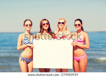summer vacation, holidays, travel, advertising and people concept - group of smiling young women with big white blank billboard on beach - stock photo
