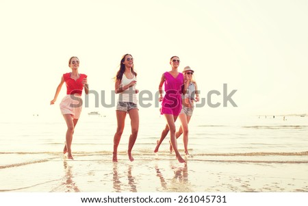 summer vacation, holidays, travel and people concept - group of smiling young women in sunglasses and casual clothes running on beach - stock photo