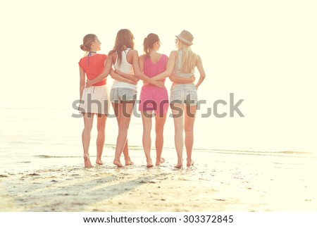 summer vacation, holidays, travel, friendship and people concept - group of young women walking on beach - stock photo