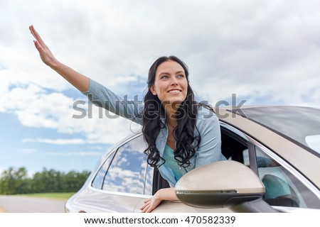 summer vacation, holidays, travel, road trip and people concept - happy young woman driving in car and waving hand