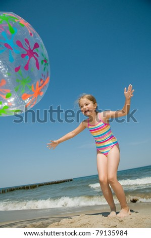 Summer vacation - little girl  playing on the beach (no name inflatable ball)