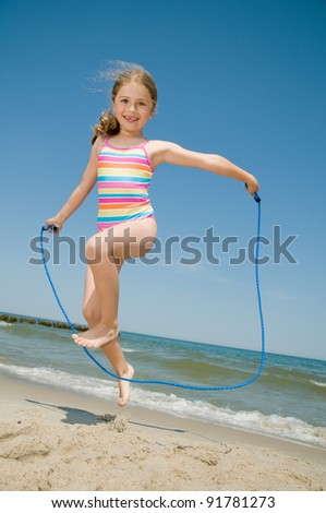 Summer vacation - little girl with skipping rope on the beach