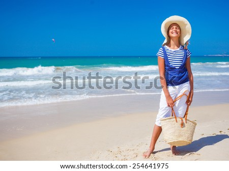 Summer vacation, lovely girl walking on the beach near water