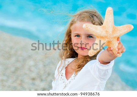 Summer vacation - lovely girl with starfish at the beach - stock photo