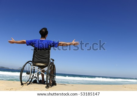 summer vacation: man in wheelchair enjoying outdoors beach - stock photo