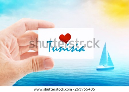 Summer Vacation on Tunisia Beach, Person Holding Visiting Card for Summertime Holiday Message Love Tunisia and Sailboat at Sea in Background. - stock photo