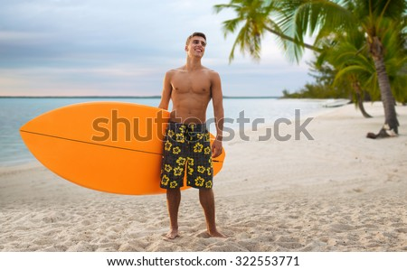 summer vacation, people, travel and water sport concept - smiling young man with surfboard or stand up paddle board over tropical beach and palm trees beach background - stock photo