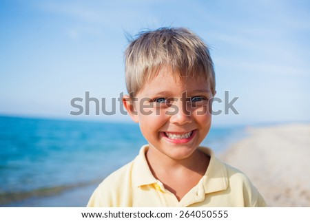Summer vacation - Portrait of lovely boy walking on the beach near water - stock photo