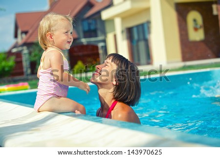 Summer vacation. Pretty little girl with her mother in swimming pool outdoors.