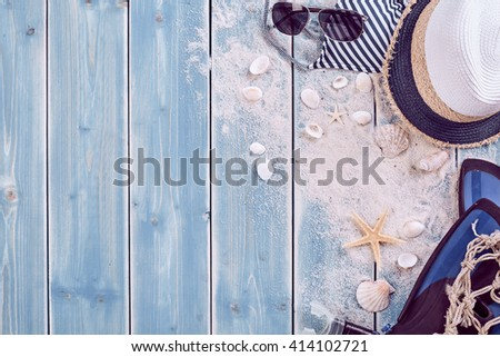 Summer vacation relaxation background theme with seashells, loose sand, hat, sunglasses and weathered wood blue background with copy space