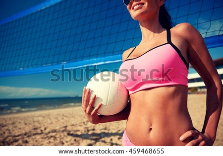 summer vacation, sport and people concept - close up of young woman with volleyball ball and net on beach - stock photo