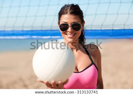 summer vacation, sport and people concept - young woman with volleyball ball and net on beach - stock photo