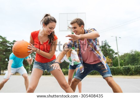 summer vacation, sport, games and friendship concept - group of happy teenagers playing basketball outdoors - stock photo