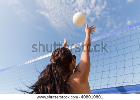 summer vacation, sport, leisure and people concept - young woman playing volleyball on beach and catching ball - stock photo