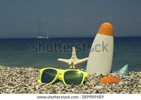 Summer vacation symbols on the pebbly beach    - stock photo