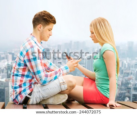 summer, vacation, technology, addiction and friendship concept - couple with smartphones sitting on bench over city background - stock photo