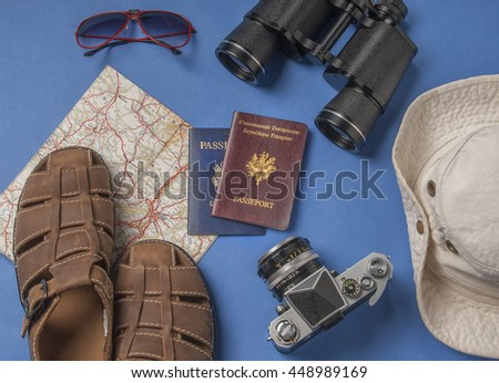 summer vacation, tourism and objects concept - close up of clothes, camera, binoculars, passports and travel map - stock photo