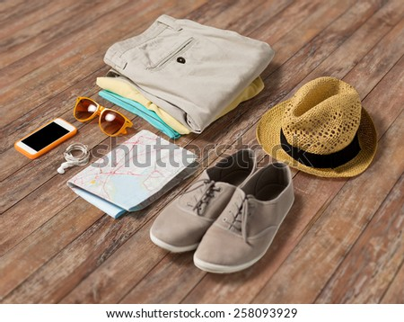 summer vacation, tourism and objects concept - close up of clothes, smartphone, personal stuff and travel map on wooden floor - stock photo