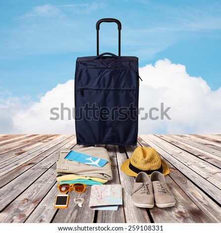 summer vacation, tourism and objects concept - travel bag, map, air ticket and clothes with personal stuff over wooden floor and blue sky background - stock photo