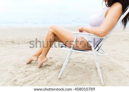 summer vacation, tourism, travel, holidays and people concept - close up of young woman sunbathing in lounge or folding chair on beach - stock photo