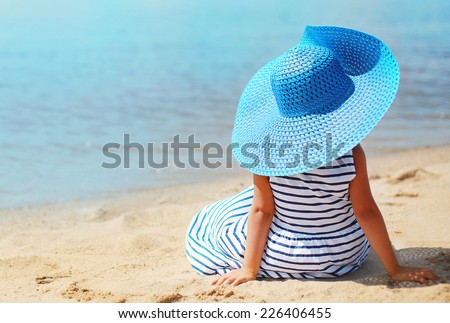 Summer, vacation, travel and people concept - pretty little girl in dress and hat enjoying on the beach near sea - stock photo
