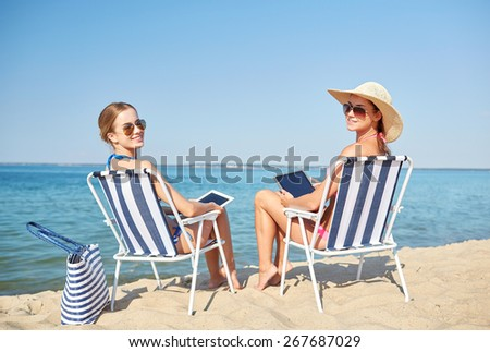 summer vacation, travel, technology and people concept - happy women with tablet pc computers sunbathing in lounges on beach - stock photo