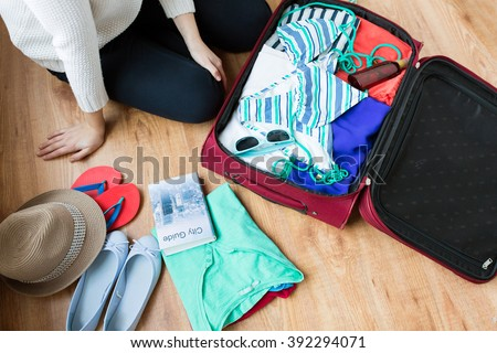 summer vacation, travel, tourism and objects concept - close up of woman packing travel bag for vacation - stock photo