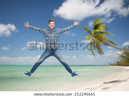 summer vacation, travel, tourism, freedom and people concept - smiling young man jumping in air over tropical beach background - stock photo