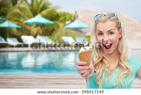 summer vacation, travel, tourism, junk food and people concept - young woman or teenage girl in sunglasses eating ice cream over beach on touristic resort background - stock photo