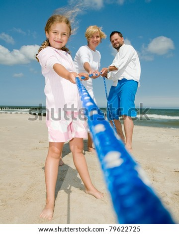 Summer vacation - Tug of war - family playing on the beach