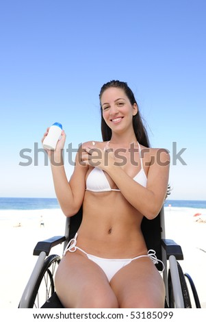 summer vacation: woman in wheelchair applying sunscreen on the  beach - stock photo