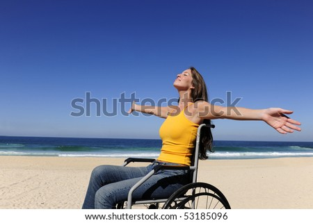 summer vacation: woman in wheelchair  sunbathing outdoors beach - stock photo