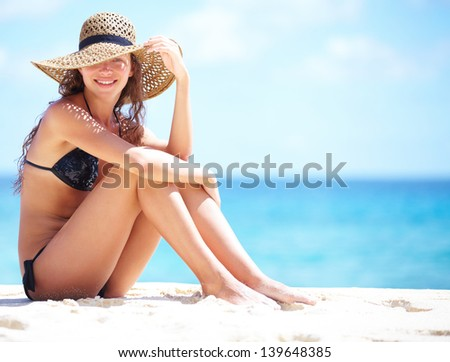 Summer vacation woman on beach in beach hat enjoying summer holidays looking at the ocean - stock photo
