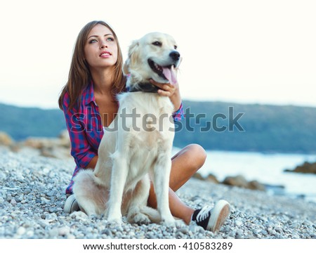 Summer vacation - woman with a dog on a walk on the beach - stock photo