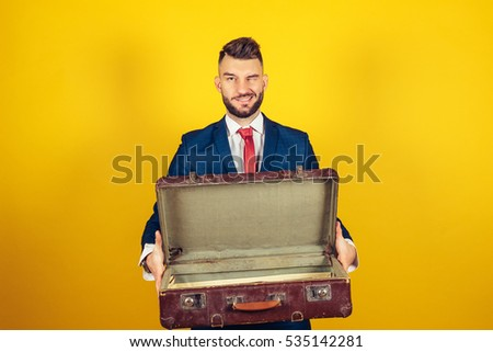 Summer vacations and travel. Happy and successful businessman is posing with suitcase on yellow background. Man with luggage on yellow background